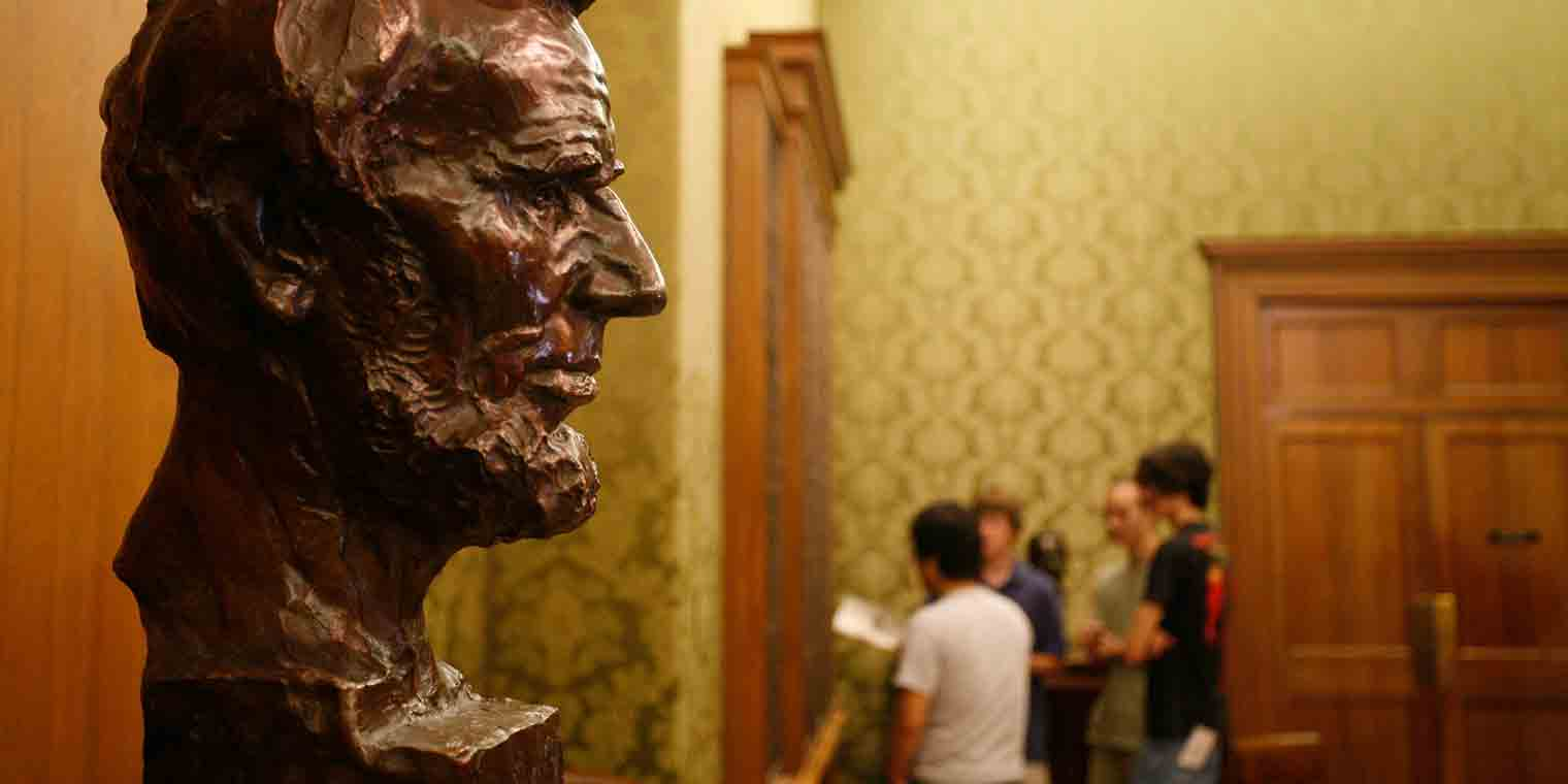 Students gather behind the bust of Lincoln at the IU Lilly Library
