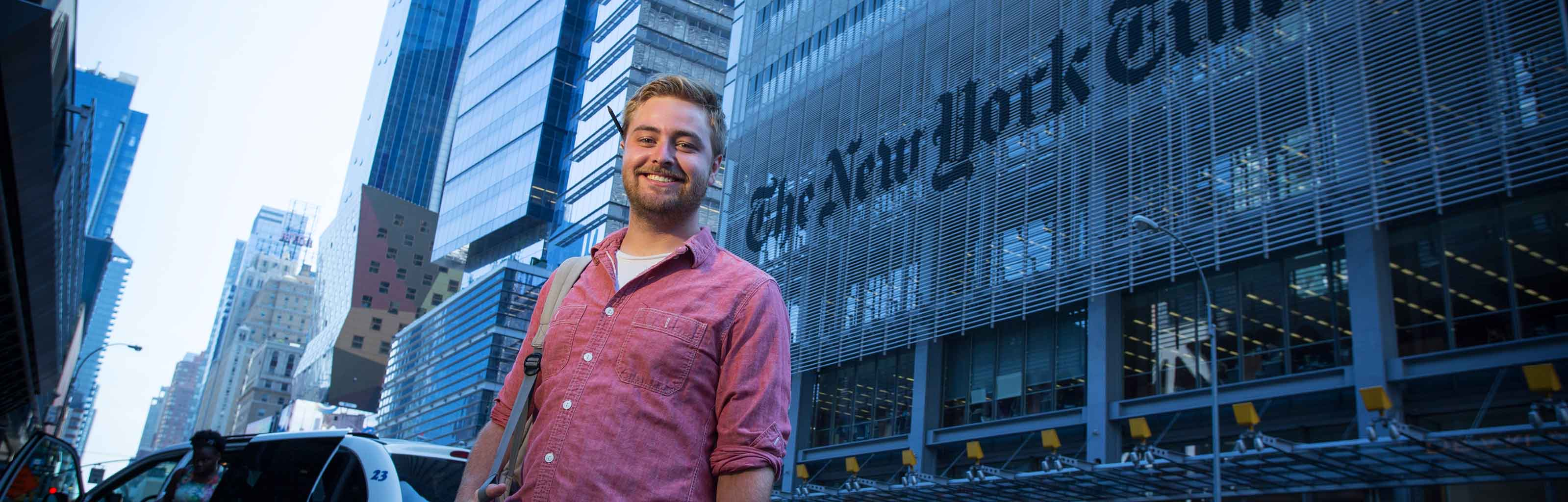An IU Alumnus standing in front of the New York Times building.