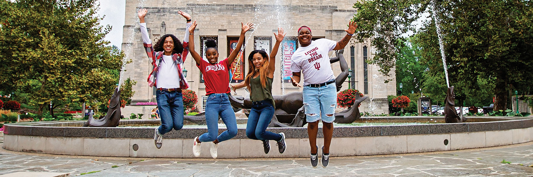 Students jumping by the fountain.