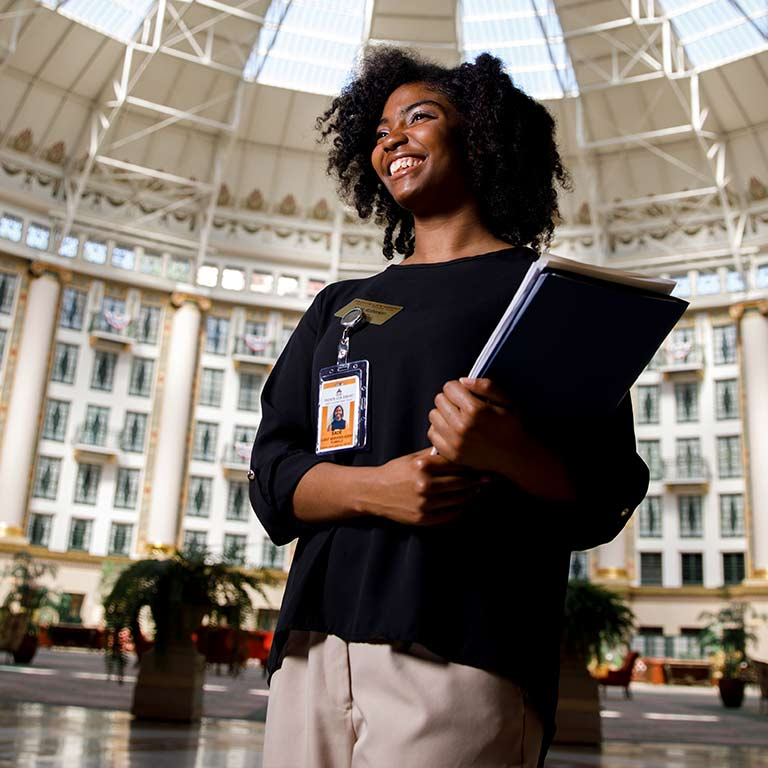 A student carrying a folder walks through the West Baden Springs Hotel.
