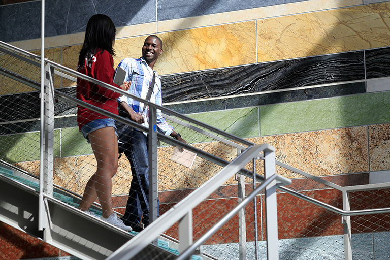 Two students walk down the atrium stairs at the SGIS building.