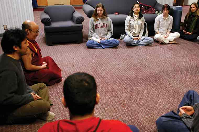 Students meditate with Buddhist monk