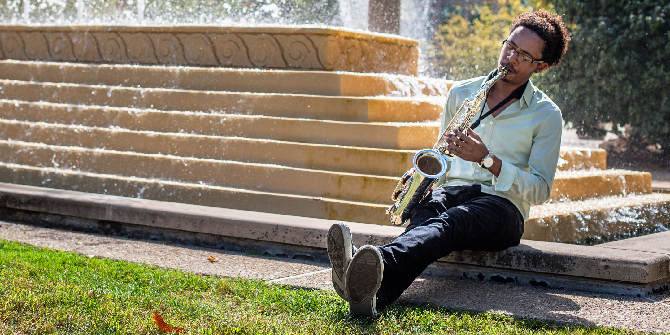 Student plays saxophone outside near a fountain.