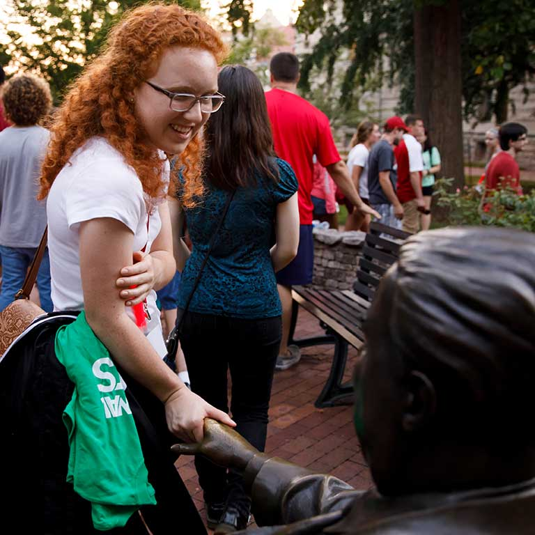 A student touches the hand of the Herman B Wells statue near Dunn's Woods.