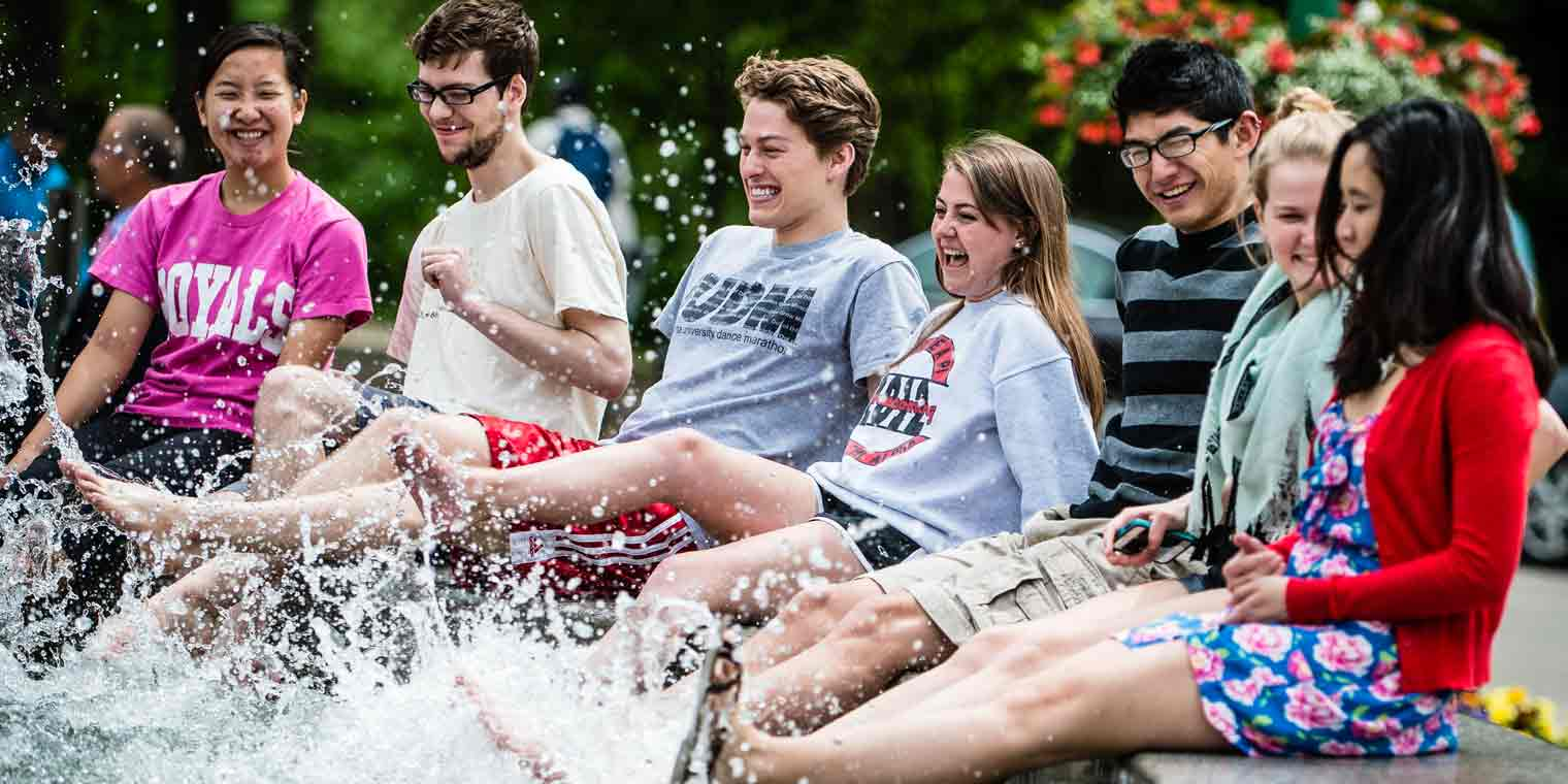 Students dipping their feet in Showalter fountain