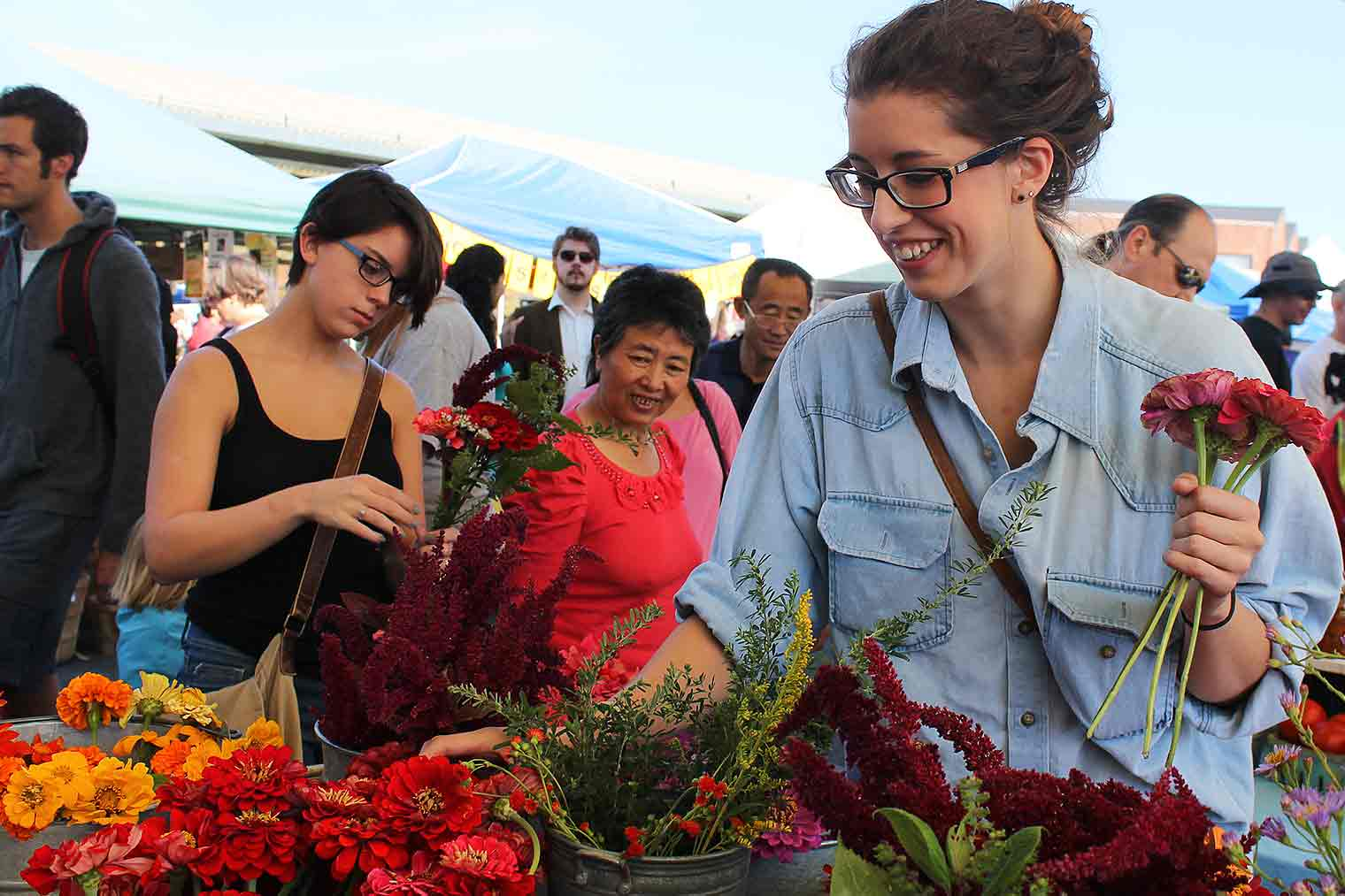 Two students purchasing flowers at the farmers' market